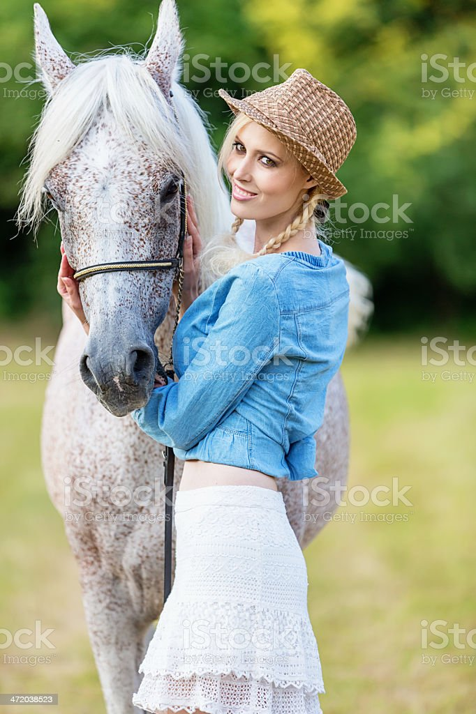 Beautiful young woman together with white horse royalty-free stock photo