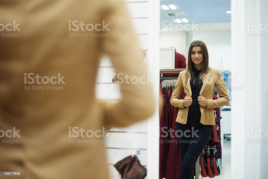 Beautiful young woman trying on jacket in front of mirror stock photo