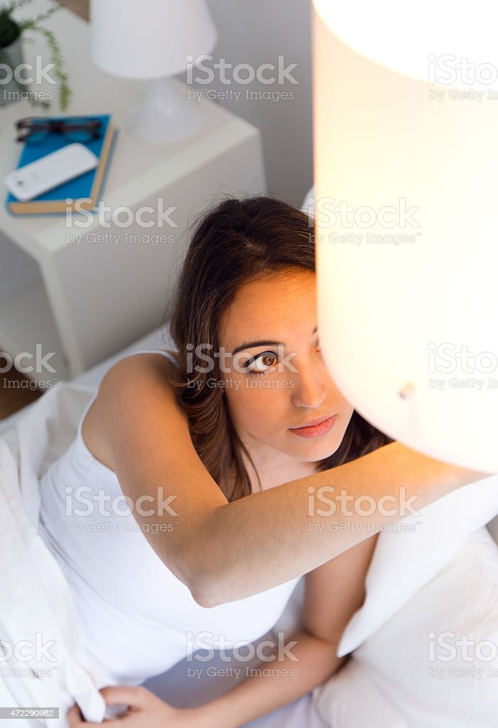 Beautiful young woman turning off the lamp. stock photo