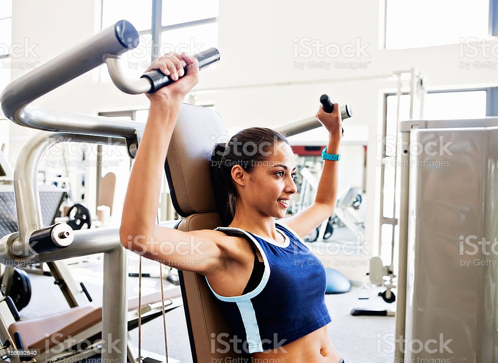 Beautiful young woman uses gym equipment to improve fitness stock photo
