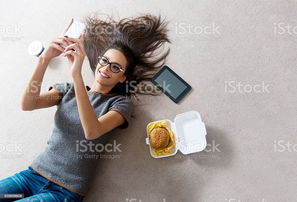Beautiful young woman using a cell phone, on the carpet stock photo