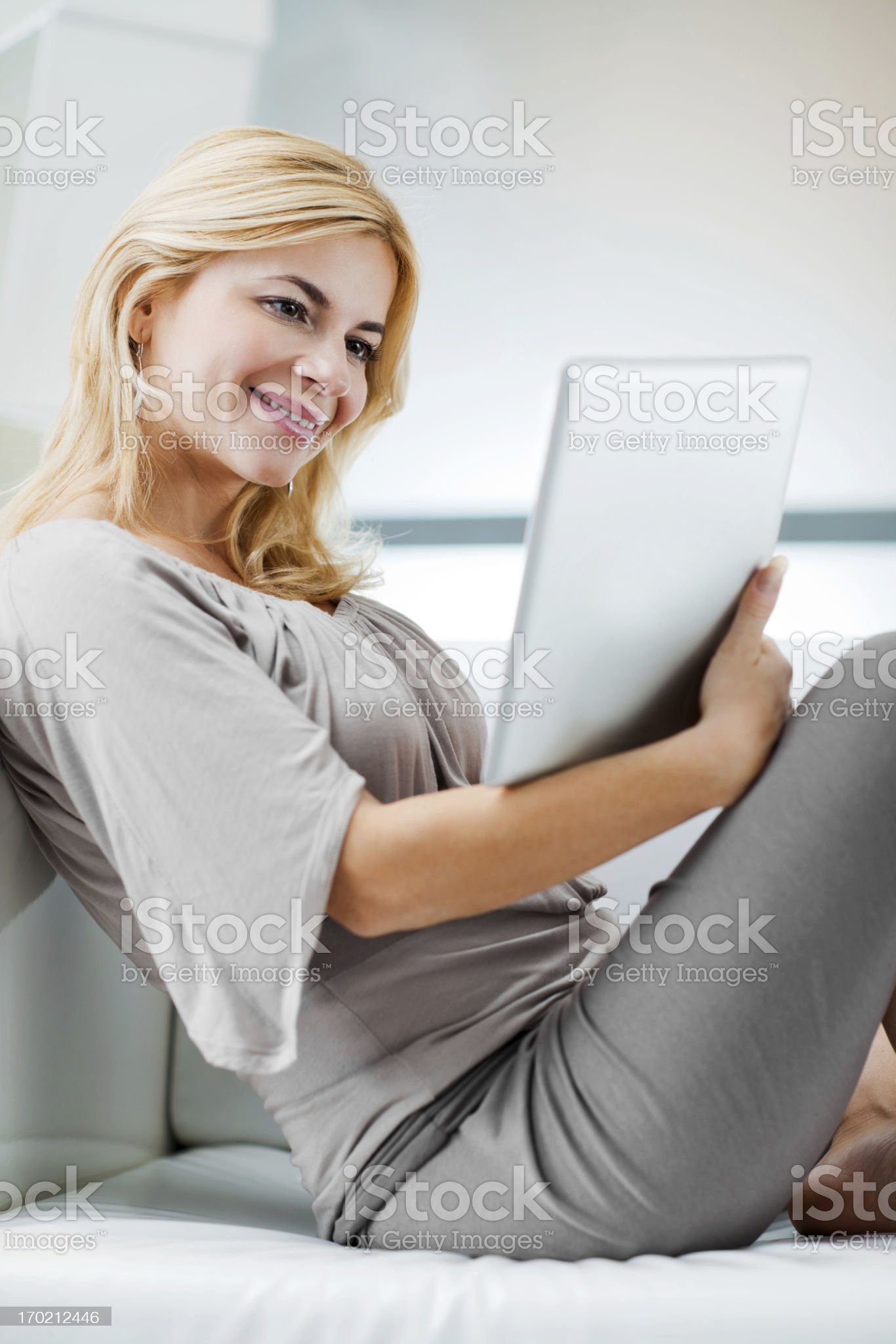 Beautiful young woman using her digital tablet at home. royalty-free stock photo