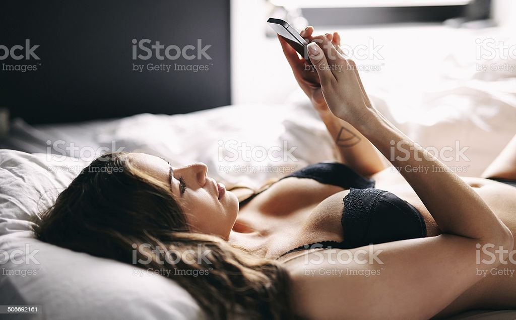 Beautiful young woman using her mobile phone stock photo