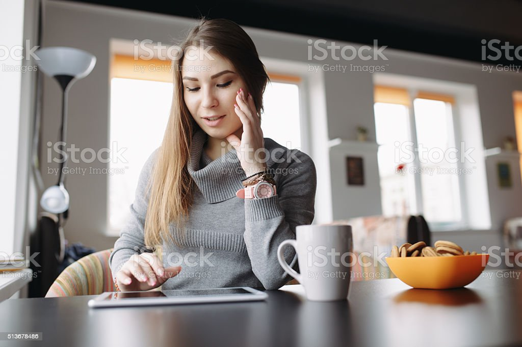 Beautiful young woman using her tablet at coffee shop stock photo