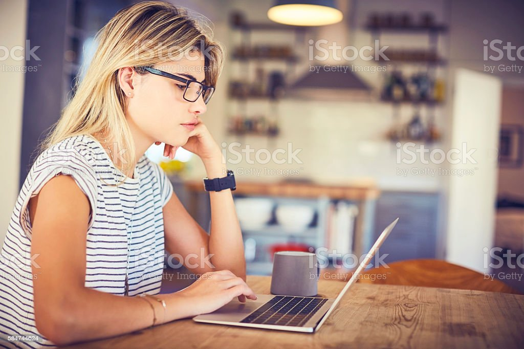 Beautiful young woman using laptop at kitchen table stock photo