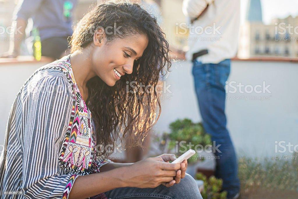 Beautiful young woman using mobile phone on a rooftop party stock photo