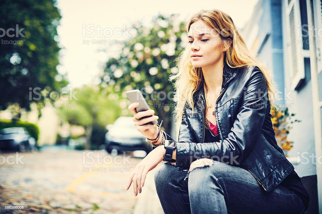 Beautiful young woman using smart phone on sidewalk stock photo