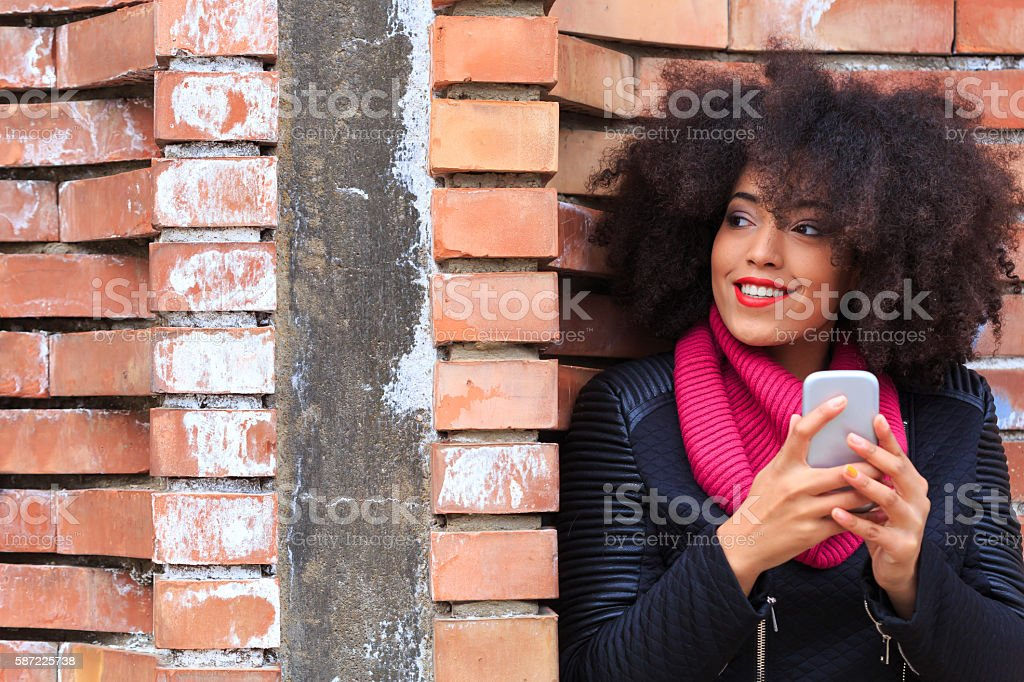 Beautiful young woman using smart phone on street stock photo
