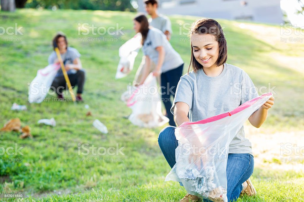 Beautiful young woman volunteering to clean up the park stock photo