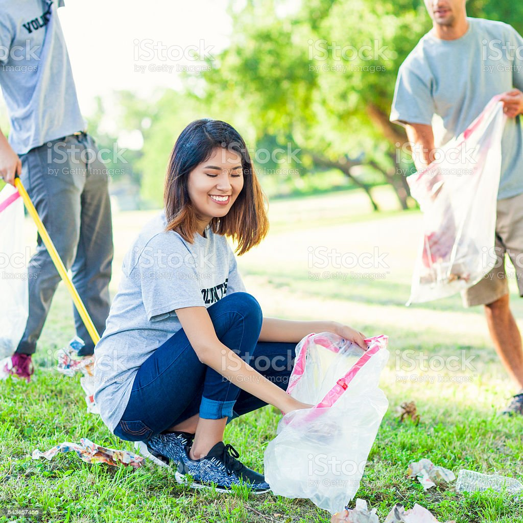 Beautiful young woman volunteers in local park stock photo