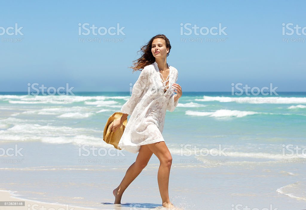 Beautiful young woman walking on beach in summer dress stock photo
