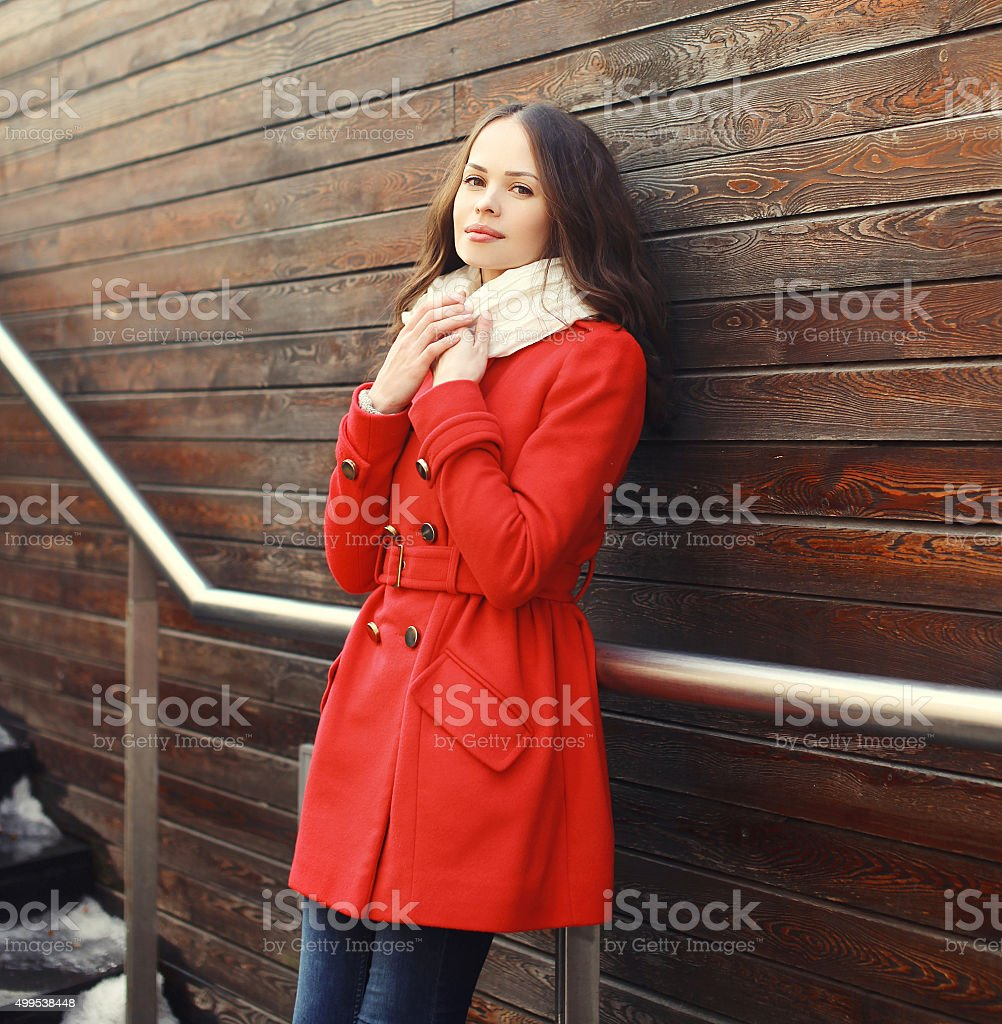 Beautiful young woman wearing a red coat and scarf stock photo