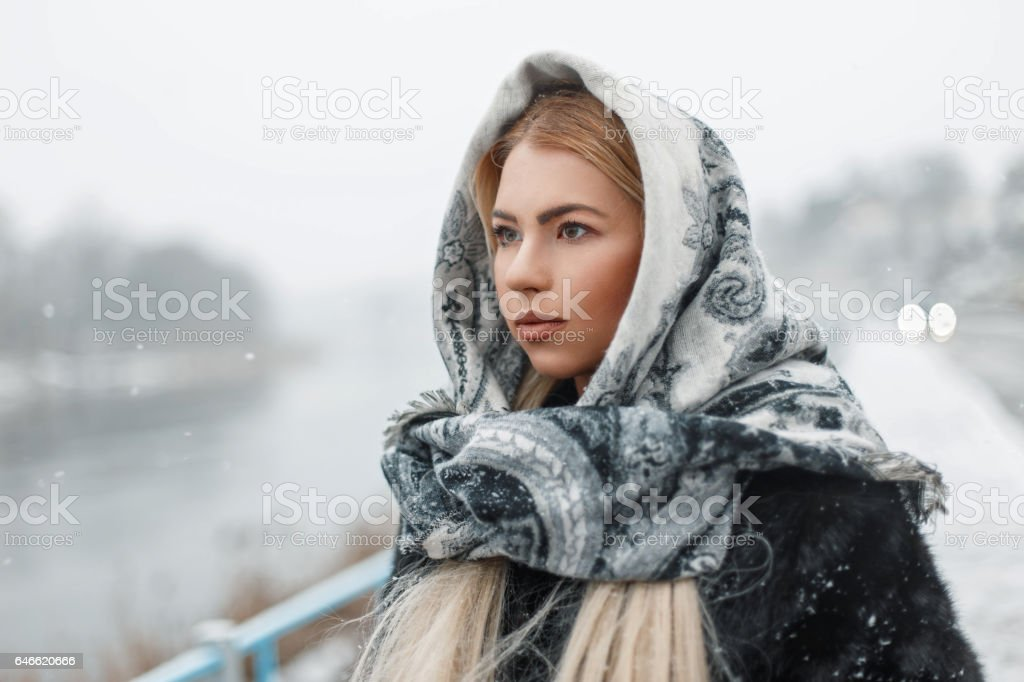 Beautiful young woman wearing a scarf in winter snowy day stock photo