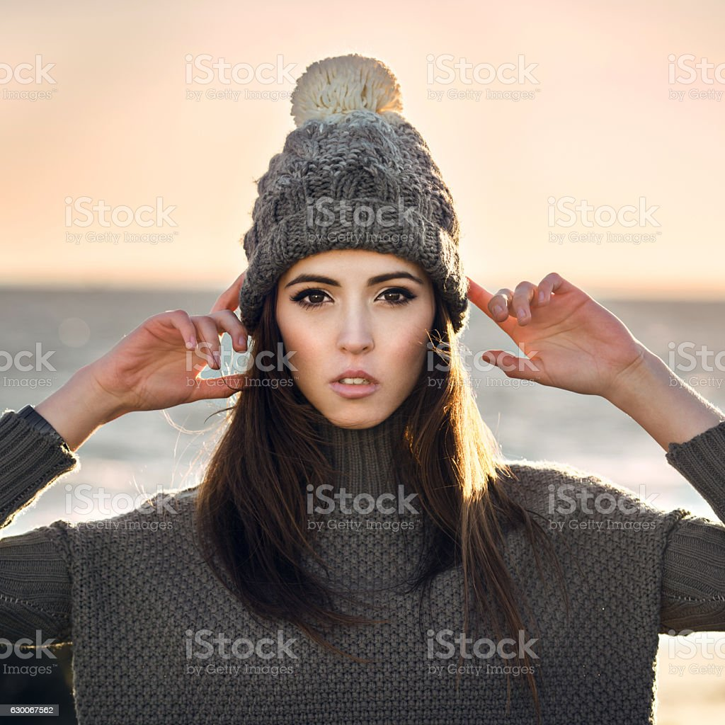Beautiful young woman wearing grey knitted hat and sweater stock photo