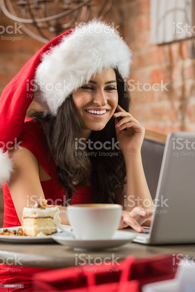 Beautiful young woman wearing Santa's hat using laptop stock photo