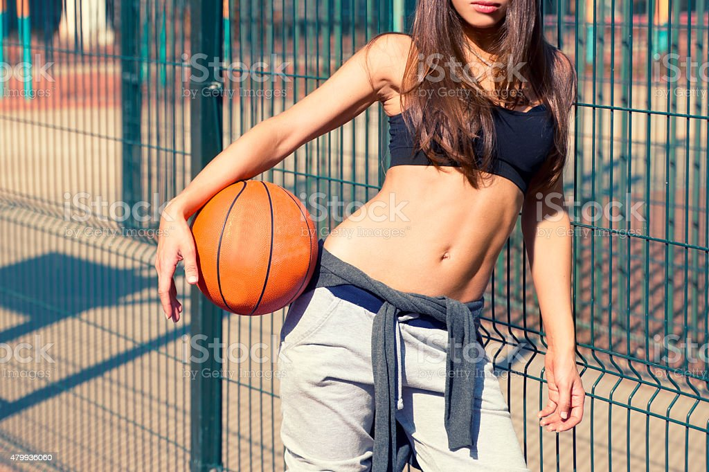 Beautiful young woman with a basketball stock photo