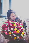 Beautiful young woman with a bouquet of roses and blurred