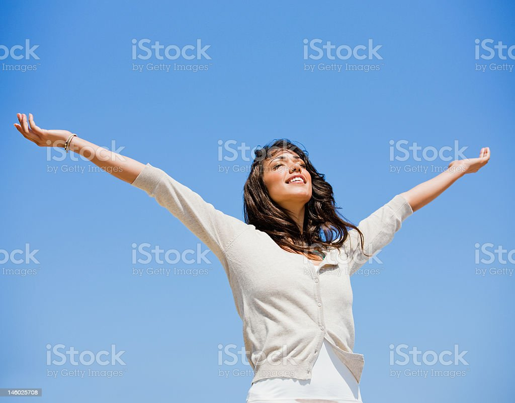 Beautiful young woman with arms raised royalty-free stock photo