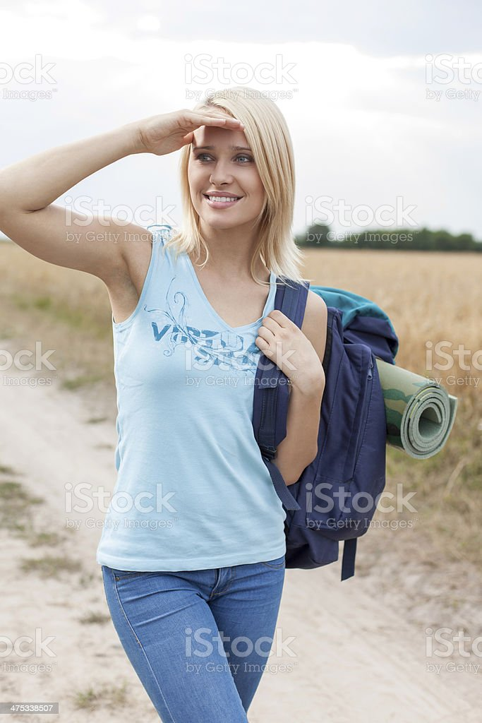 Beautiful young woman with backpack hiking at field stock photo