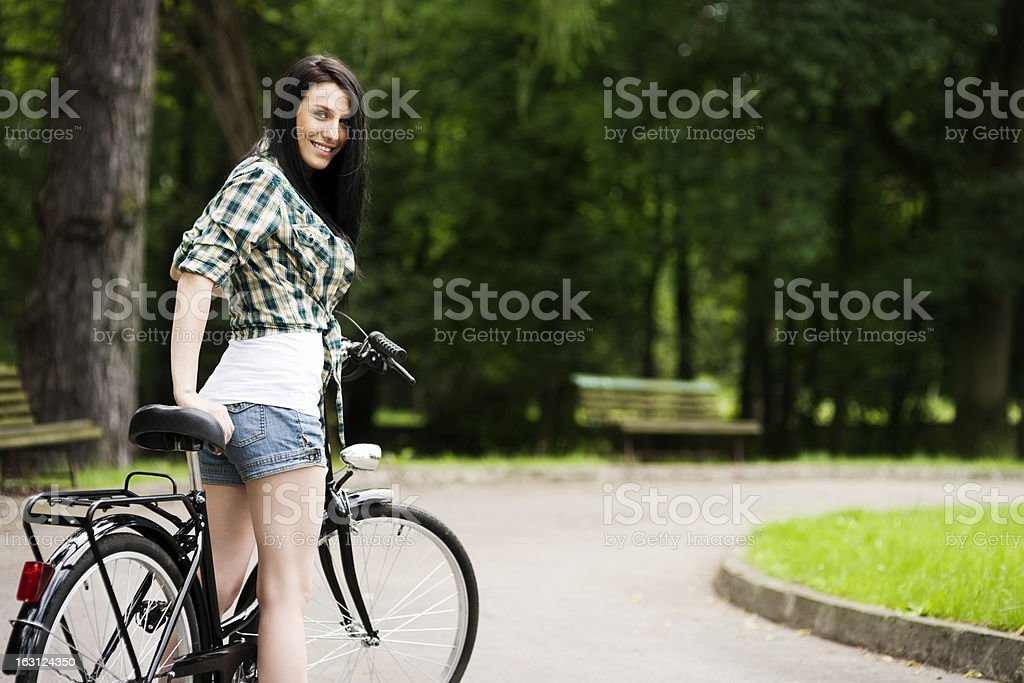 Beautiful young woman with bicycle in park royalty-free stock photo