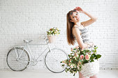 Beautiful young woman with bike on backgraund and bascket full