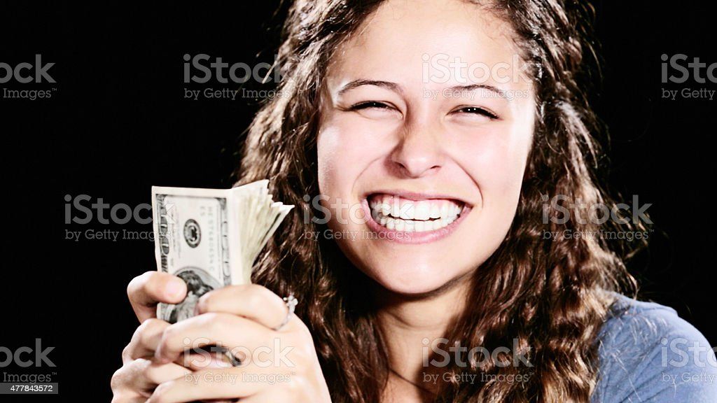 Beautiful young woman with bundle of money gives beaming smile stock photo