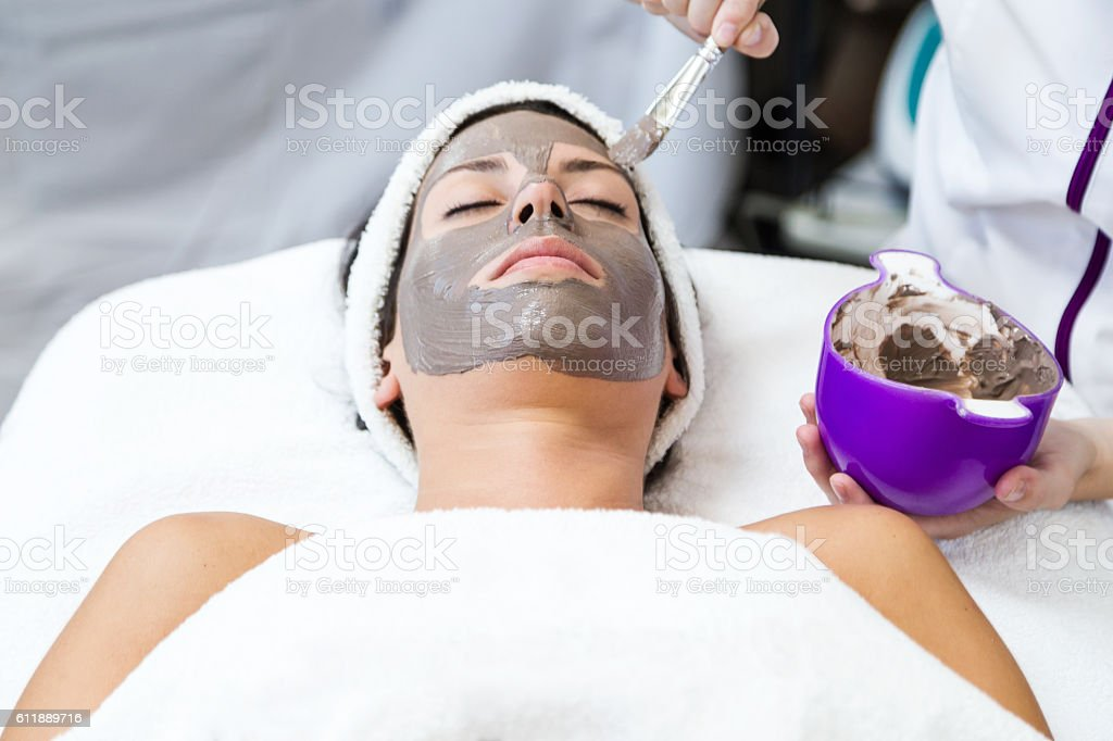 Beautiful young woman with clay facial mask in beauty spa. stock photo