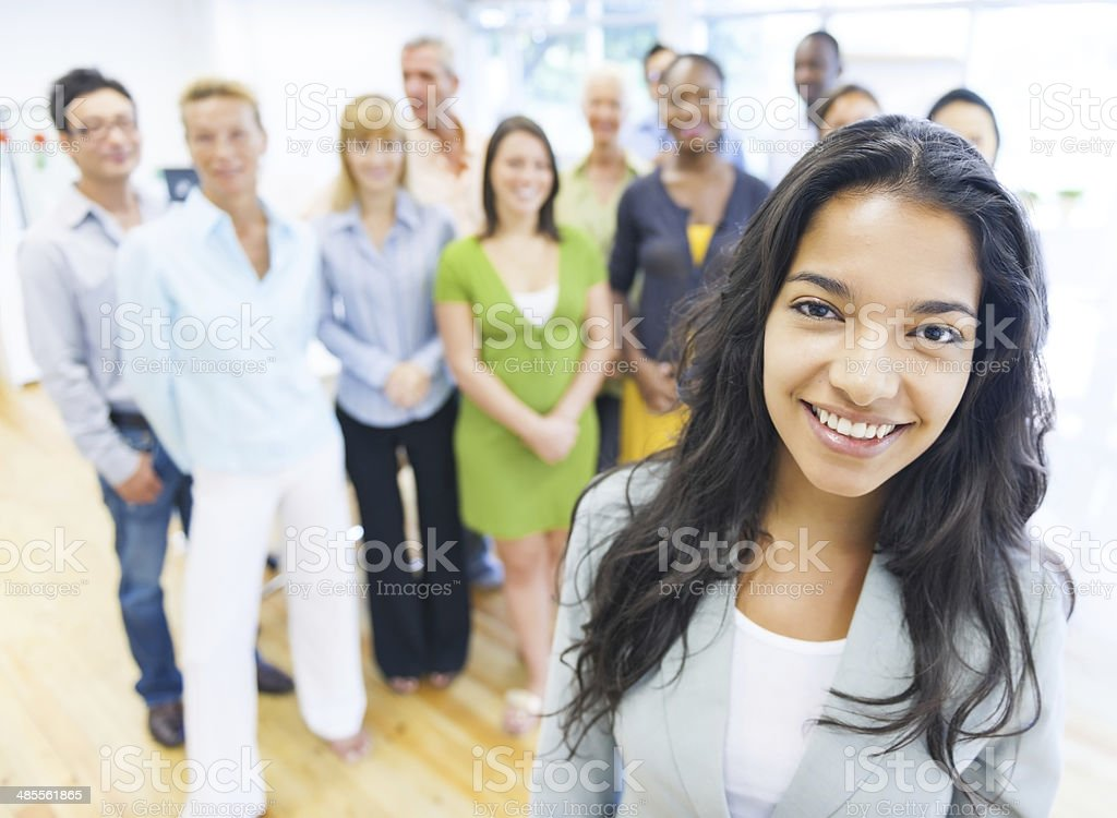 Beautiful young woman with colleagues in the background stock photo