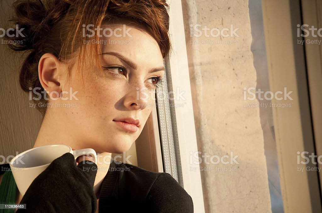Beautiful young woman with cup of coffee over window royalty-free stock photo