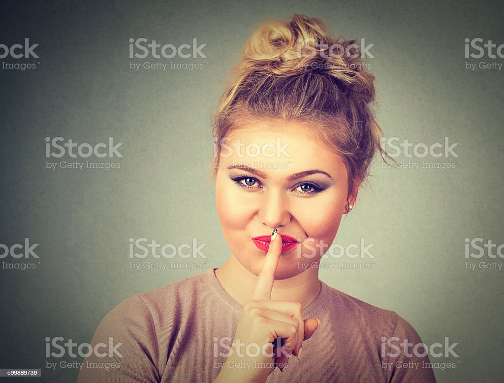 beautiful young woman with finger on lips stock photo