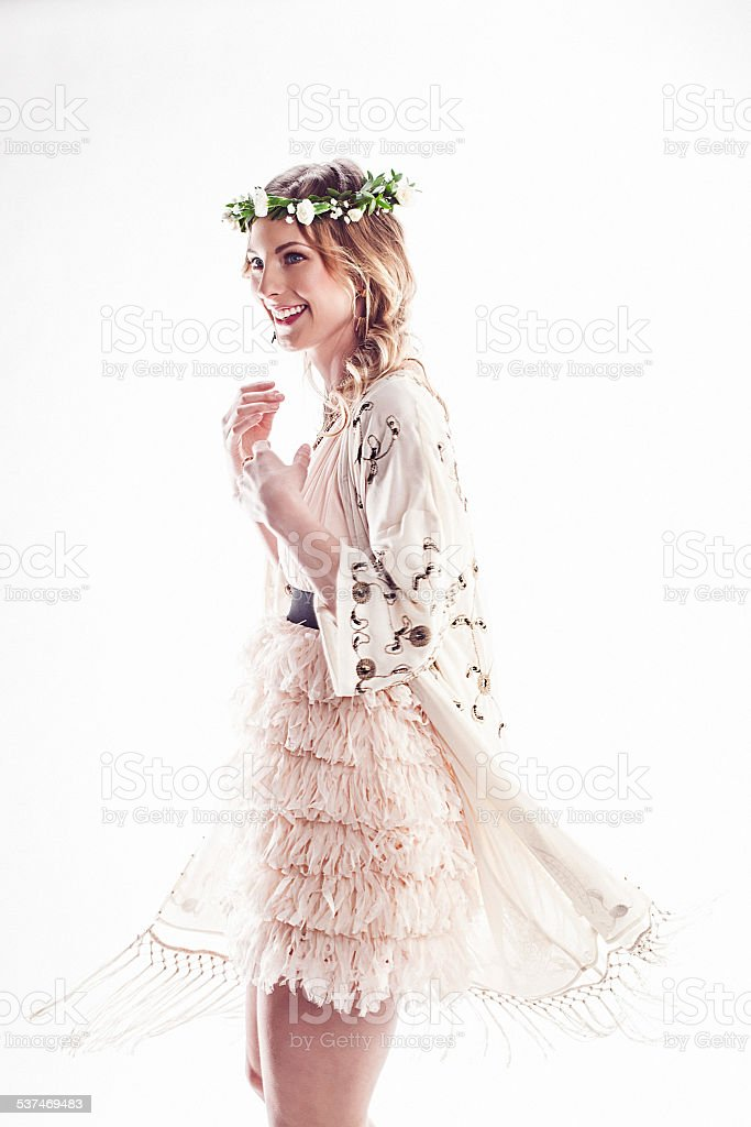 Beautiful young woman with flower wreath in her hair dancing stock photo