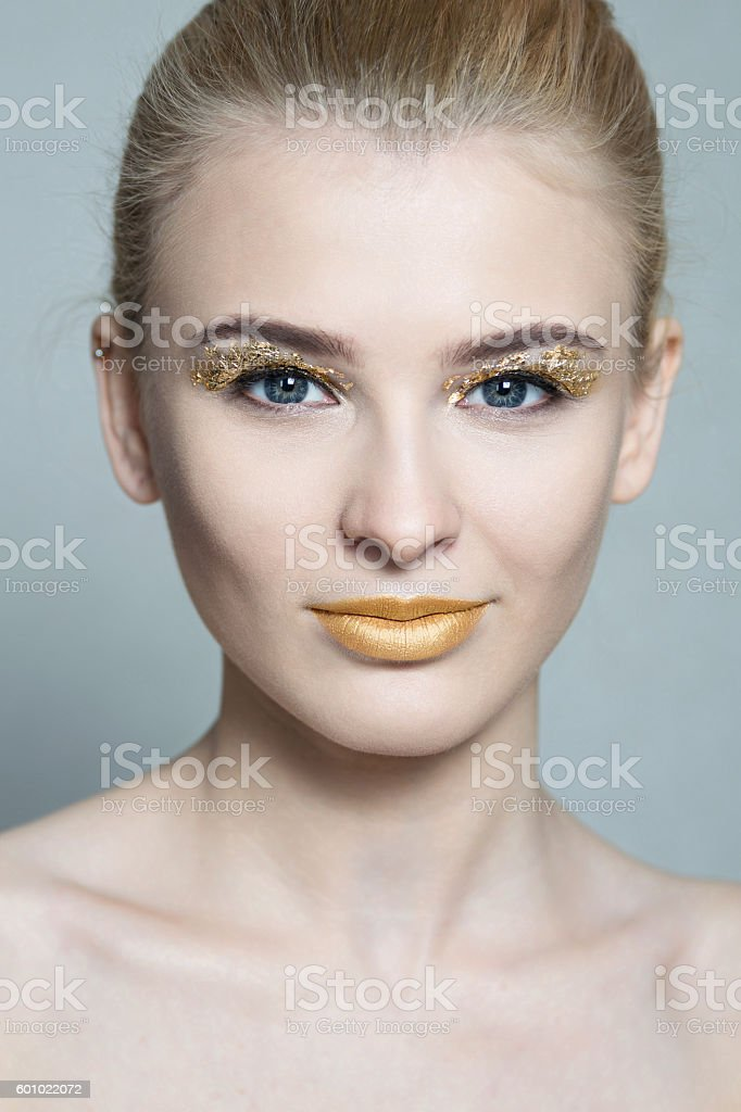 beautiful young woman with golden lips and golden foil on eyes stock photo