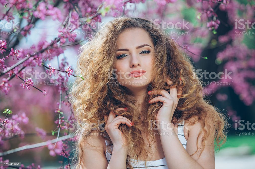 Beautiful young woman with gorgeous curly fair outdoors,flowering stock photo