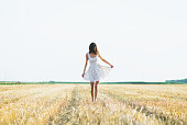 Beautiful young woman with hat in the field