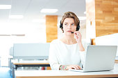 Beautiful young woman with headset working in call center