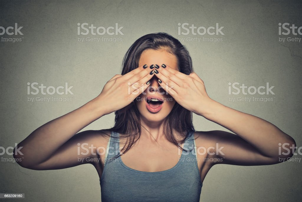 Beautiful young woman with her eyes covered by hands stock photo