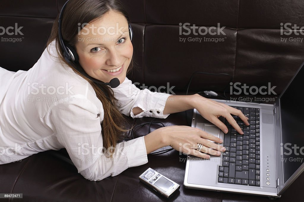 beautiful young woman with laptop, cell phone and headset royalty-free stock photo