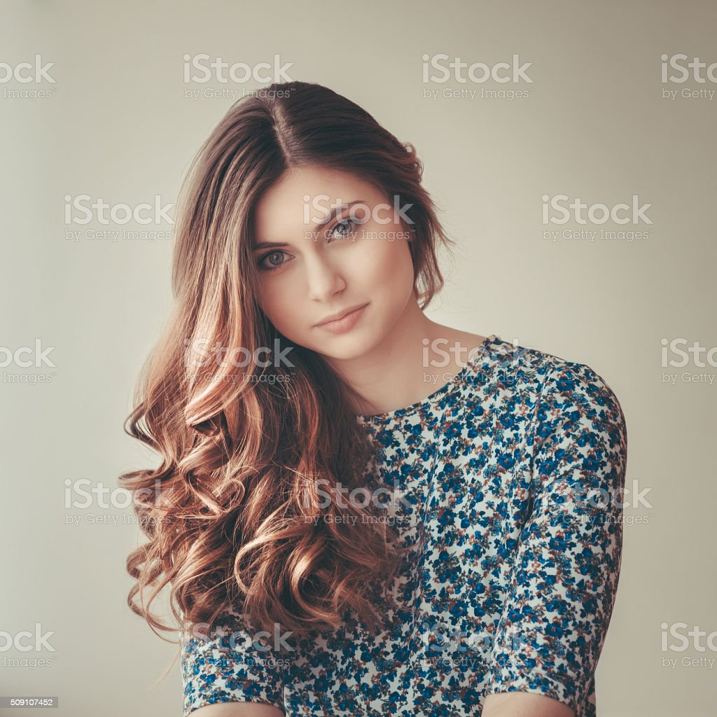 Beautiful young woman with long curly red hair stock photo