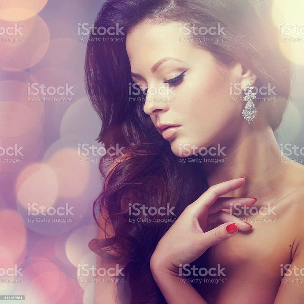 Beautiful young woman with long hair and jewelery. stock photo