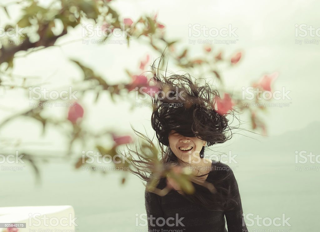 Beautiful young woman with long hair blowing and smiling royalty-free stock photo