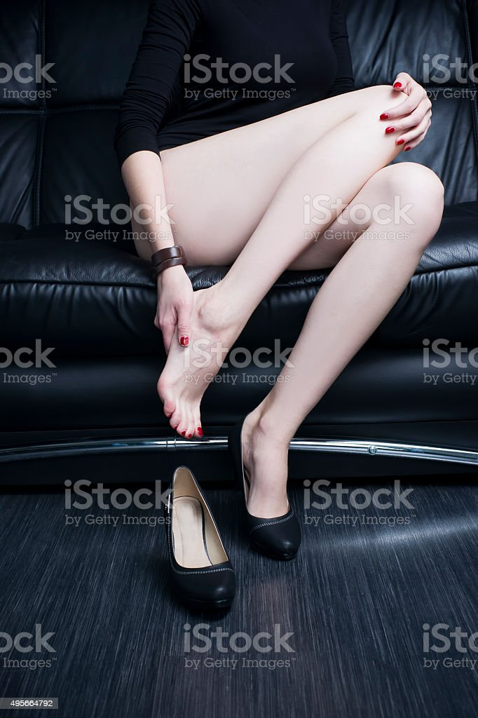 Beautiful young woman with long legs in bodysuit. Leg pain stock photo