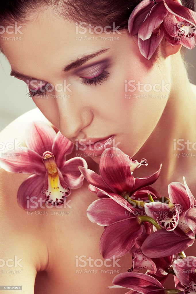 Beautiful young woman with orchid flowers royalty-free stock photo
