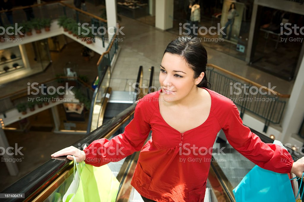 Beautiful Young Woman with Shopping Bags on Mall Escalator royalty-free stock photo