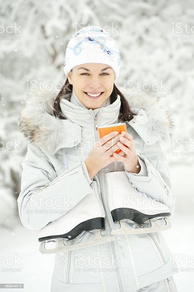 Beautiful young woman with skate and cup of hot drink royalty-free stock photo