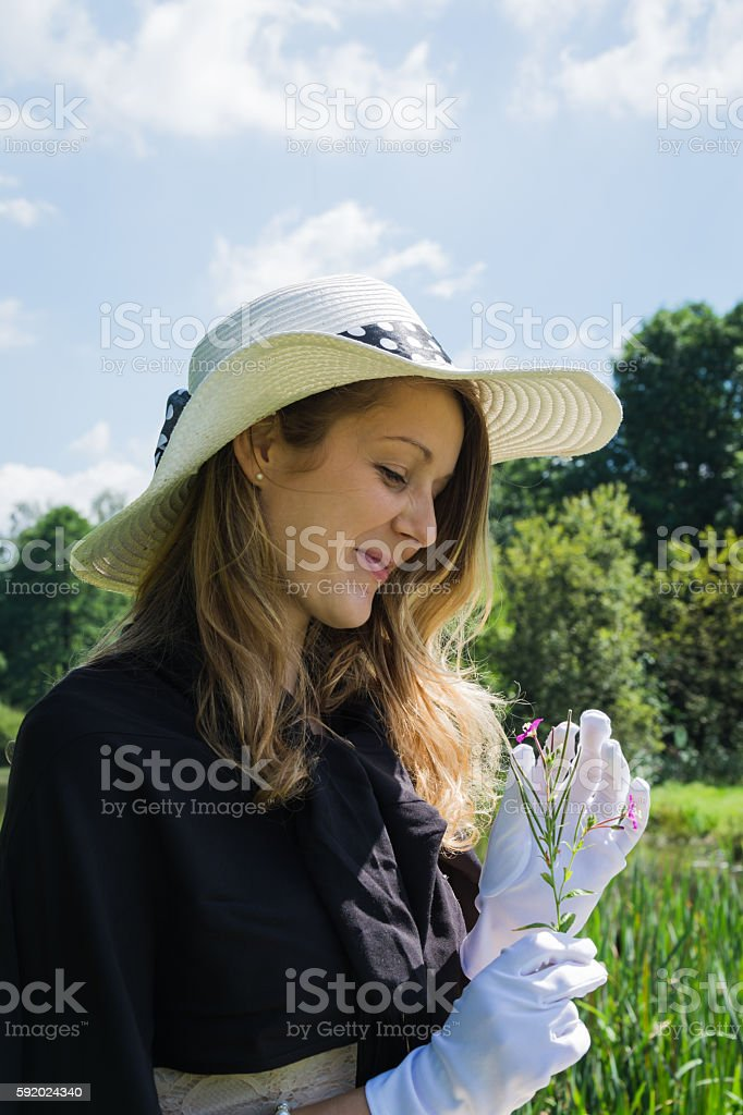 Beautiful young woman with white gloves and flower stock photo