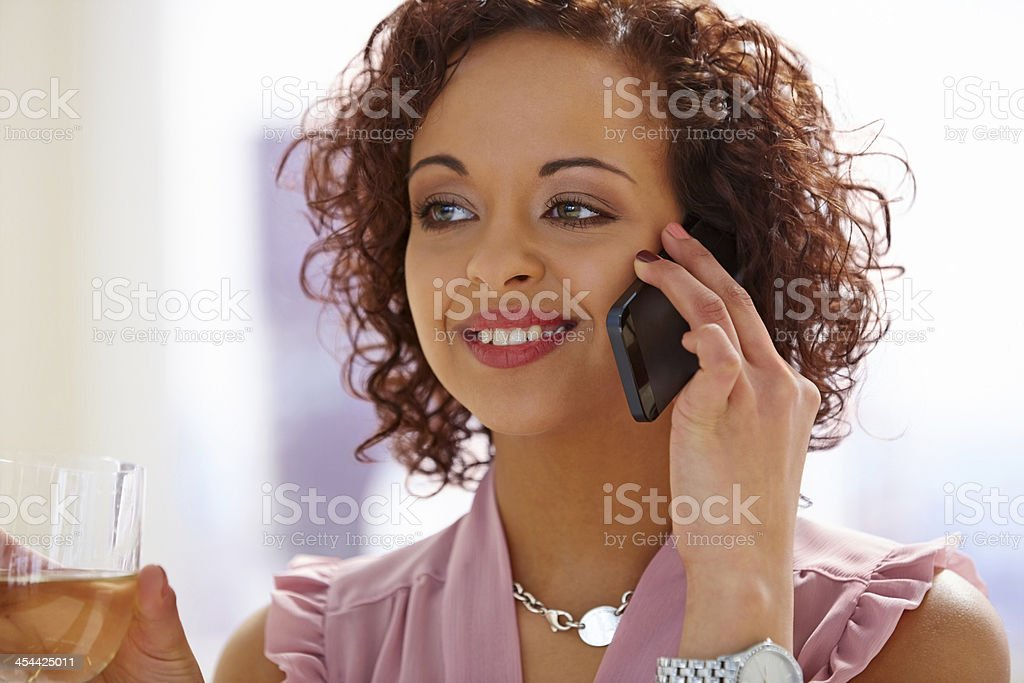 Beautiful young woman with wine making a phone call royalty-free stock photo