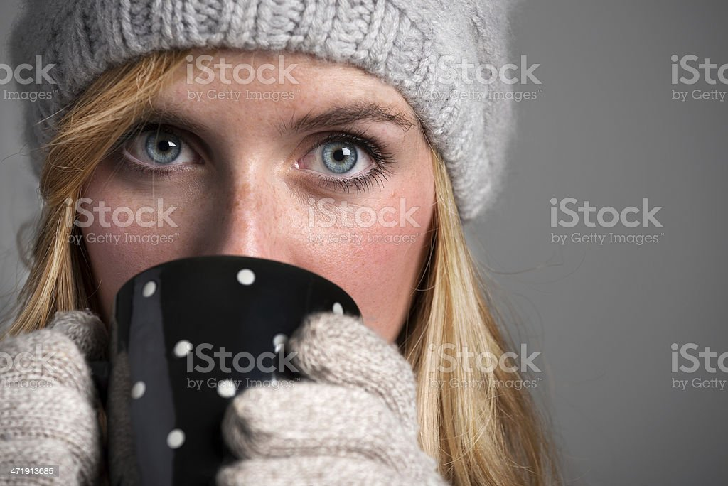 Beautiful young woman with winter hat and gloves drinking coffee royalty-free stock photo