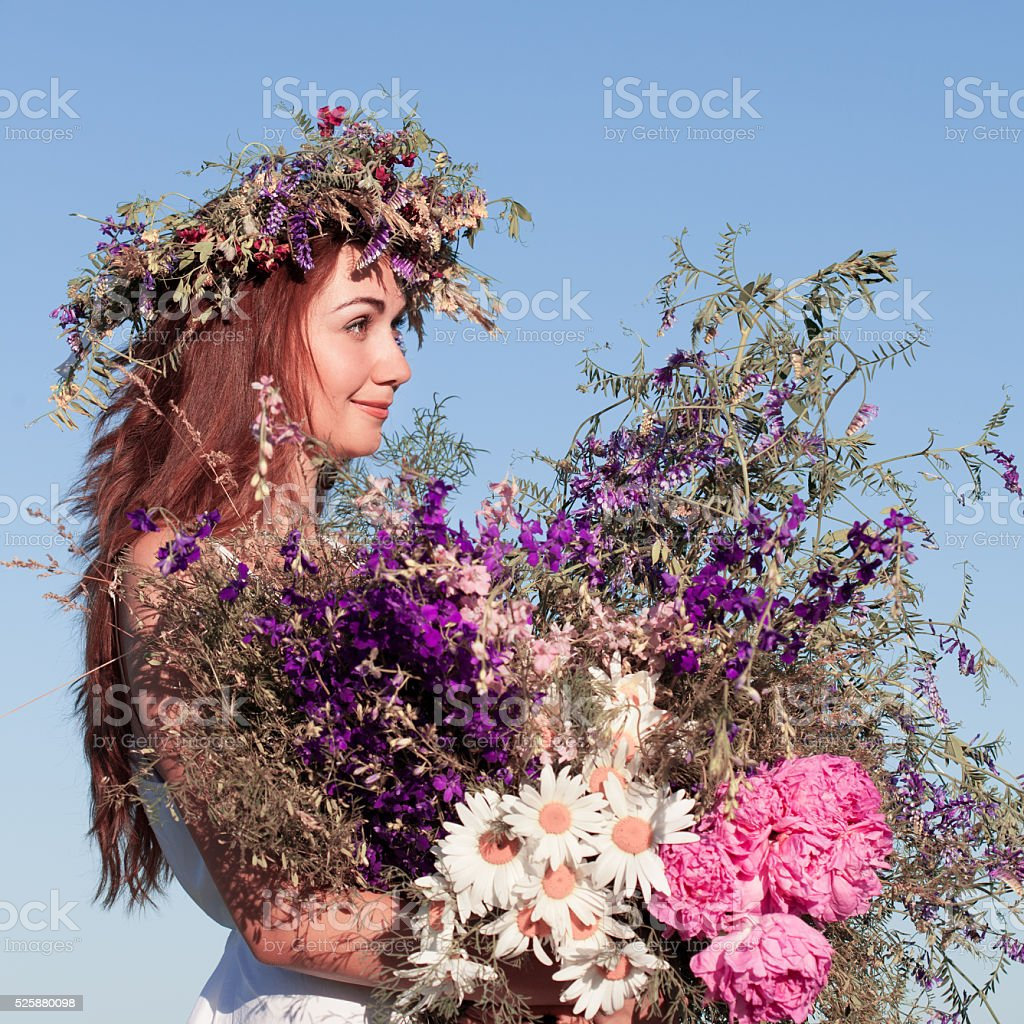 Beautiful young woman with wreath of wildflowers in their hair stock photo