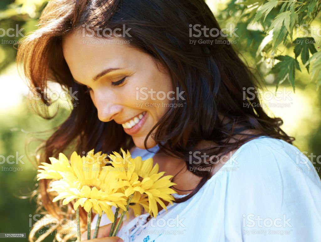 Beautiful young woman with yellow flowers in a park royalty-free stock photo