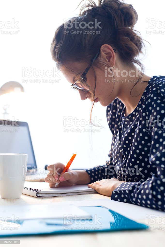 Beautiful young woman working in her office. stock photo